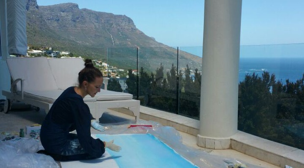 Jeannine Platz hand painting her Suite View of Camps Bay at Atlantique Villa Camps Bay